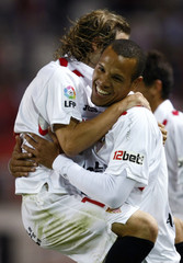 Sevilla's Luis Fabiano is congratulated by team mates after scoring against Atletico Ciudad in Seville