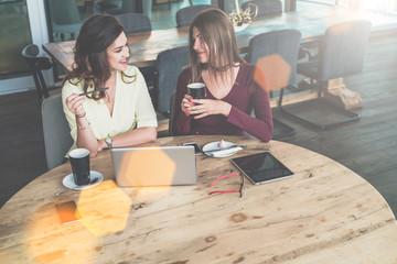 On desk is laptop and digital tablet.Girls blogging,shopping,learning online. Brainstorming, teamwork.