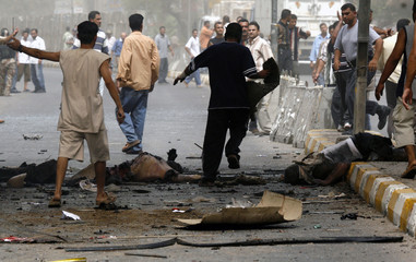 Bodies lie on a road shortly after a bomb exploded inside a minibus in Baghdad