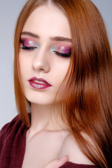 Pretty young redghead woman's studio portrait on gray background, pink makeup