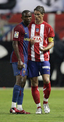Atletico Madrid's Fernando Torres talks to Barcelona's Samuel Eto'o during their Spanish First Division soccer match at Atletico Madrid's Vicente Calderon stadium in Madrid