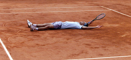 GUSTAVO KUERTEN LIES IN THE MIDDLE OF A HEART HE DREW IN CENTRE COURT.