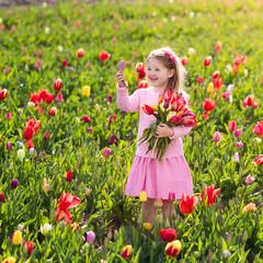 Wall Mural - Little girl in tulip flower garden