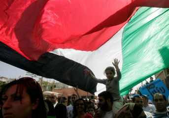 Demonstrators walk under a Palestinian flag during rally in Jaffa