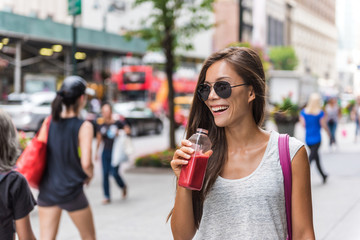 Urban city lifestyle hipster asian woman drinking healthy fruit vegetable berry juice smoothie walking on downtown street of New York city, NYC, USA. Happy young adult health diet concept.