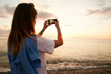 A girl making picture of the sunset on the sea on her phone