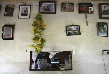 Photographs of Makereta Cagi's late husband hang from a wall in her house as she works in the kitchen of her house in Fiji's capital Suva