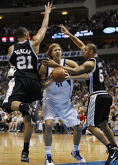 Mavericks Nowitzki of Germany drives between Spurs Duncan and Udoka during NBA Western Conference quarterfinal playoff basketball game in Dallas