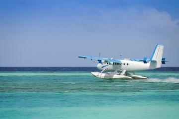 Seaplane taking off over blue ocean