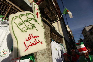 An oversized foam hand is hung up by a fan in support of the national soccer team, in Algiers