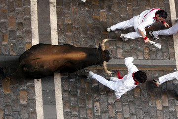 RUNNERS EVADE FIGHTING BULL ON ESTAFETA STREET IN PAMPLONA.