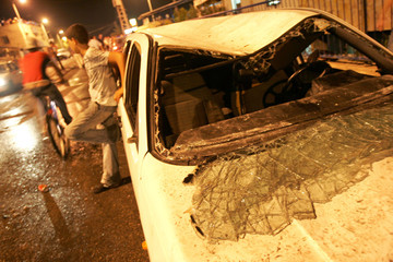 An Israeli youth stands next to a damaged car after a shooting attack in the town of Shfaram.