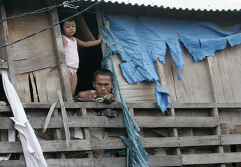 A father and his daughter gaze through the window in the slums of northern Jakarta