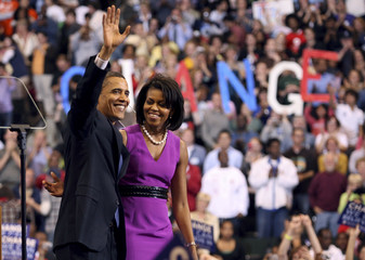 US Democratic presidential candidate Senator Barack Obama (D-IL) waves to the crowd wth his wife Michelle at his side after delivering his speech at his South Dakota and Montana presidential primary election night rally at the Xcel Energy Center in St. Pau