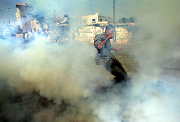 A Palestinian man runs after Israeli soldiers fire tear gas at protesters during a protest in Bilin.