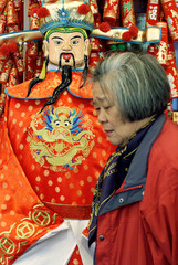 """WOMAN WALKS PAST EFFIGY OF """"GOD OF WEALTH"""" PRIOR TO LUNAR NEW YEAR INHONG KONG."""