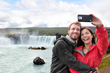 Wall Mural - Selfie couple taking smartphone picture of Godafoss waterfall outdoors on Iceland. Couple visiting famous tourist attractions and landmarks in Icelandic nature landscape. Mixed race couple having fun.