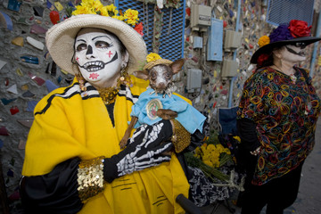 """A woman wearing a skeleton costume holds her dog during the celebration of the Day of the Death or """"Dia de los Muertos"""" in east Los Angeles"""