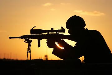 Israeli soldier aims rifle at Palestinian territory during Jewish settlers' road block in Gush Katif ...