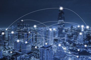 Network conection concept on blue tone aerial view of cityscape business district at twilight  background.