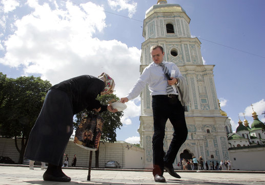 A man gives money to a woman begging in front of the 11th century St.Sofia Cathedral in central Kiev