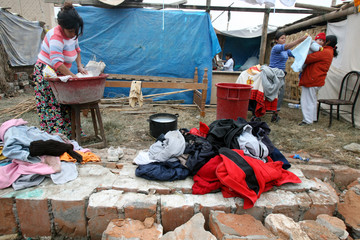 Earthquake survivor does her laundry next to her  destroyed house in Pisco
