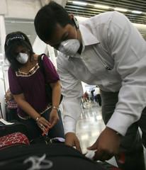 Honduran passengers wear masks before travelling from Ramon Villeda  Morales International airport in San Pedro Sula