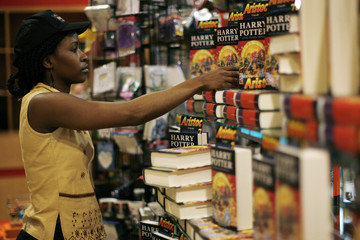 An employee stocks the shelves with the latest Harry Potter book released worldwide today, in the Aristoc Book store in the Garden City shopping centre in Kampala