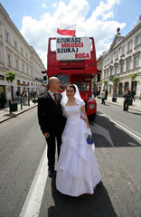 People dressed as wedding couple stand in front of bus during march in central Warsaw