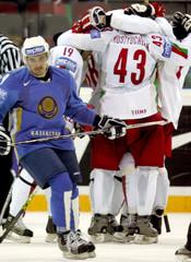 Belarus players celebrate a goal as Kazakhstan's Rifel skates away during their ice hockey World Championship match in Riga