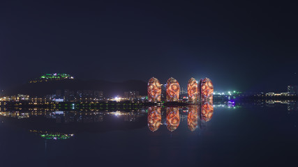 Night view of an artificial Phoenix island and Sanya city illuminated with city lights.