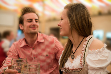 Young couple flirting in Oktoberfest beer tent