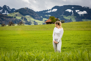 Girl on a meadow in front of the Grueyeres Village in Switzerland