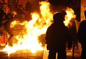 Policemen protect themselves from a Molotov cocktail during riots in Athens