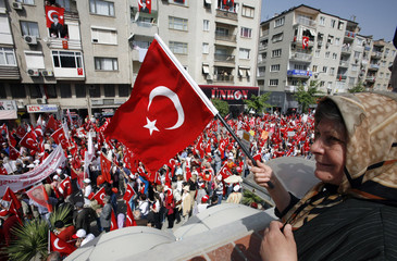 A woman waves national flag woman as tens of thousands of people march during an anti-government rally in western Turkish city of Manisa