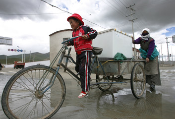 A Tibetan girl, with her mother's help, rides a tricycle to transport a refrigerator on a street in Dangxiong Country, Tibet