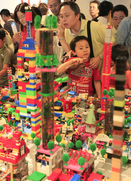 Participants look at Dream City which was built by about 100,000 pieces of Lego blocks in Tokyo
