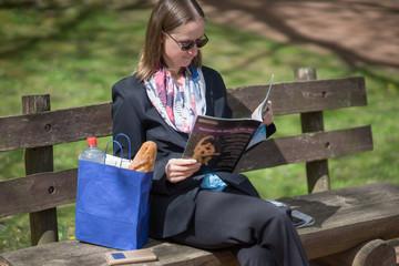 Bank mit Leserin im Park mit Picknick