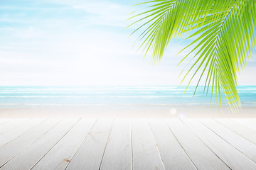 Empty wooden table and palm leafs with party on beach background blurred. Concept Summer, Beach, Sea, Relax, Party.