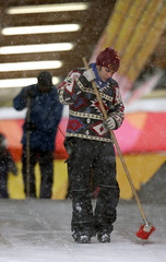 A worker cleans the start line of fresh snow during a training session for the upcoming skeleton world cup tour at the Olympic track in Cesana Pariol