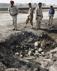 Iraqi soldiers inspect the scene of roadside bomb attacks in Basra