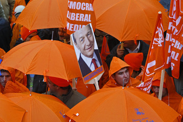 A portrait of Romania's incumbent President Basescu is seen amongst umbrellas during an electoral rally in Sibiu