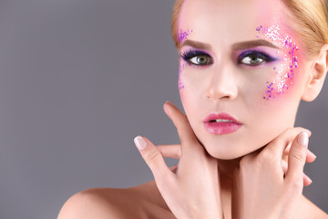 Beautiful young woman with creative makeup on color background