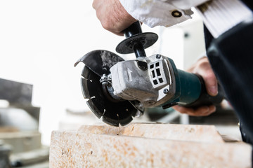 Handyman working at marble stone with disc grinder