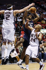 New Jersey Nets Boone and Jefferson force Cleveland Cavaliers James to pass in their NBA basketball game in East Rutherford