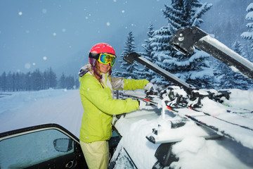 Girl fastening skis on car roof during snowfall