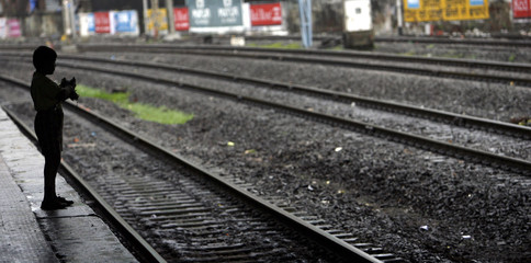 Boy waits for train at railway station in Mumbai