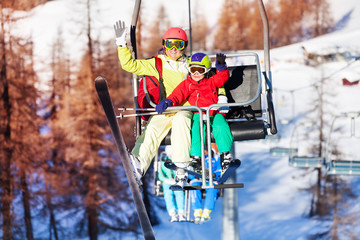 Happy skiers lifting on chairlift and waving hands