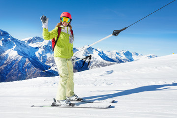Girl on button ski lift going uphill, waving hand