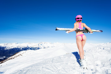 Girl in pink helmet and bikini against of mountain